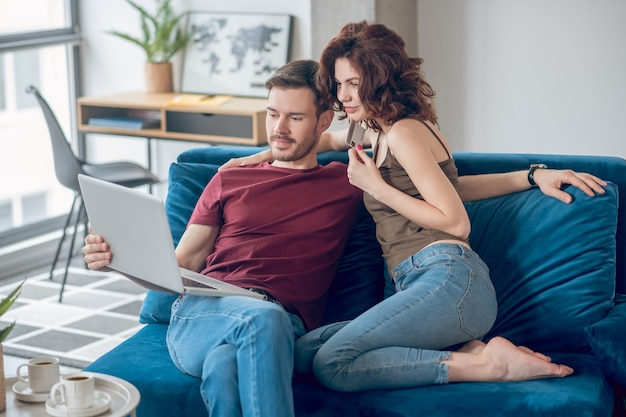 Płatności okresowe. para dokonująca okresowych płatności online i wyglądająca na zaangażowaną