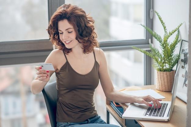 Płatności online. ciemnowłosa ładna kobieta trzyma kartę kredytową i planuje dokonać płatności online