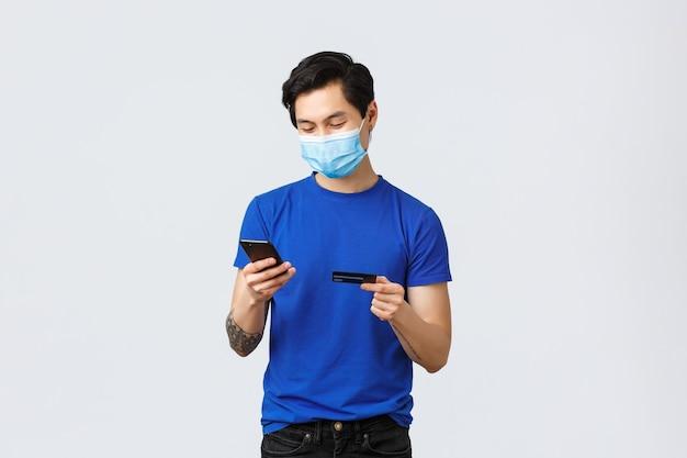 Płatności zbliżeniowe, zakupy online podczas koncepcji covid-19 i pandemii. młody beztroski facet złożyć zamówienie, wstawić cyfry karty kredytowej, aby kupić coś w internecie, pisać na telefonie komórkowym, nosić maskę.
