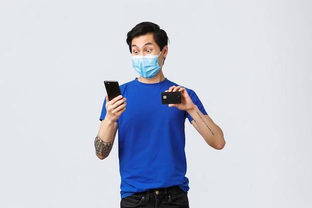 Płatności zbliżeniowe, zakupy online podczas koncepcji covid-19 i pandemii. podekscytowany i zdumiony azjata w masce medycznej, wpatrujący się zdumiony w aplikację konta bankowego na smartfonie, pokazuje kartę kredytową