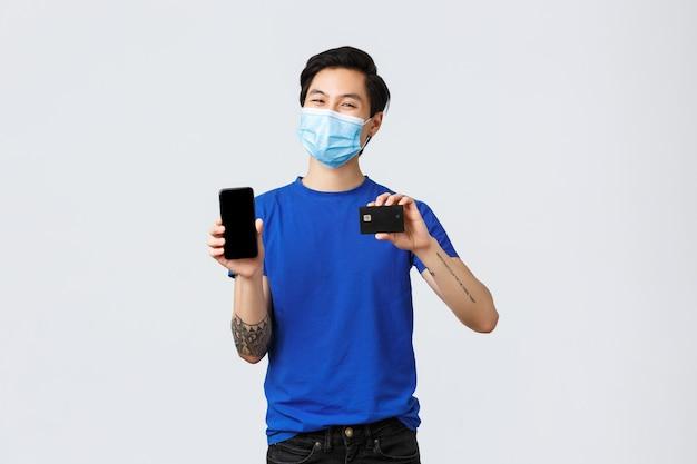 Płatności zbliżeniowe, zakupy online podczas koncepcji covid-19 i pandemii. zadowolony młody człowiek w masce medycznej, azjatycki facet pokazujący ekran smartfona i kartę kredytową, sklep internetowy