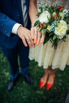 Platynowe lub srebrne pierścionki na palcach nowożeńców, zbliżenie