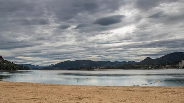 Plaża castro urdiales w dzień z szarymi chmurami.