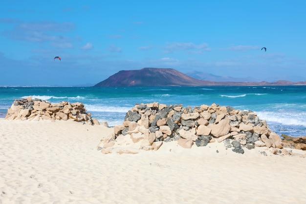 Plaża corralejo dunas z kamieniami chroni przed silnymi wiatrami, fuerteventura