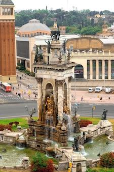 Plaza de espana, pomnik z fontanną w barcelonie, hiszpania. pochmurne niebo, ruch uliczny