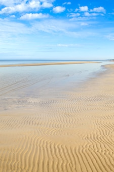 Plaża dzintari, jurmala, łotwa. falujący piasek na plaży, morze i błękitne niebo z chmurami.