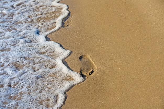 Plaża, fala i odciski stóp o zachodzie słońca