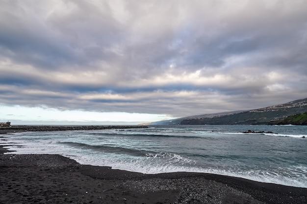 Plaża martianez z surferami czekającymi na fale