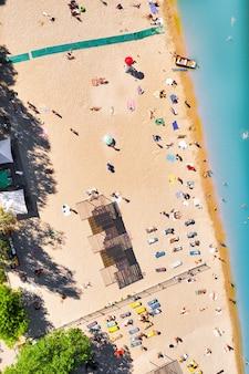 Plaża miejska z czystą lazurową wodą i mnóstwem turystów leżących na ciepłym piasku - widok z góry dronem