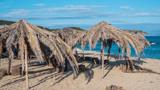Plaża morza egejskiego z parasolami wykonanymi z gałązek palmowych w grecji