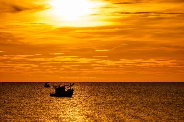 Plaża, morze podczas sezonu letniego w ranku wschodzie słońca z sylwetki łodzią rybacką.