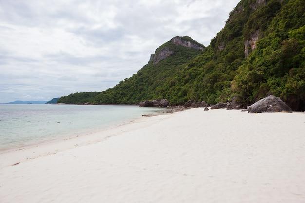 Plaża na tropikalnej wyspie. czysta, błękitna woda, piasek, chmury.