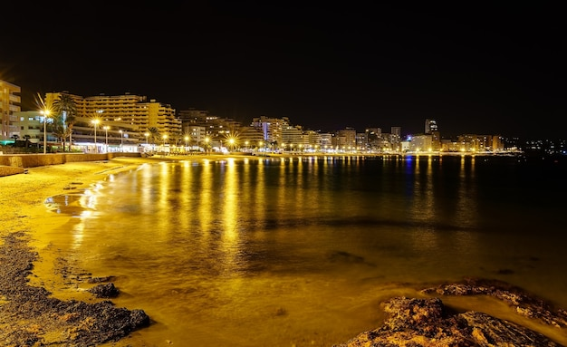 Plaża nocą z oświetlonymi budynkami i odbiciami świateł w wodzie. calpe alicante.