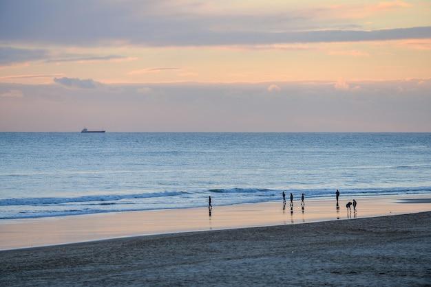 Plaża otoczona morzem i ludźmi pod zachmurzonym niebem podczas pięknego zachodu słońca