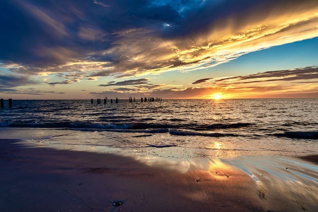 Plaża otoczona morzem z pionowymi drewnianymi deskami podczas zachodu słońca wieczorem
