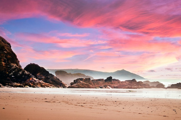 Plaża otoczona skałami i morzem pod zachmurzonym niebem podczas pięknego różowego zachodu słońca