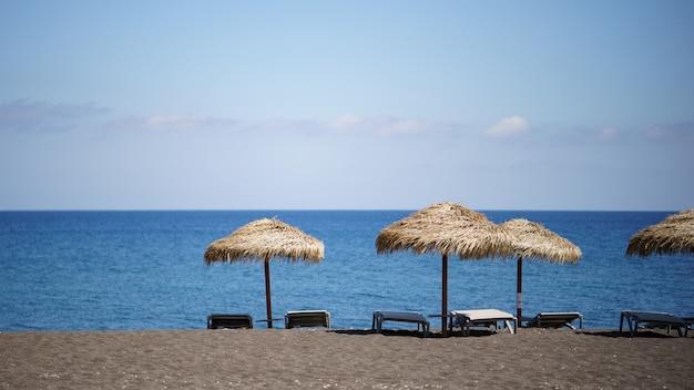 Plaża perissa pokryta czarnym piaskiem z widokiem na leżaki i parasole na santorini w grecji