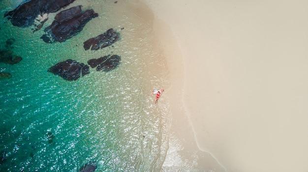 Plaża trutnia widok tropikalna wyspa phuket, biała plaża z falami, para leżąca na plaży. zdjęcie z lotu ptaka.