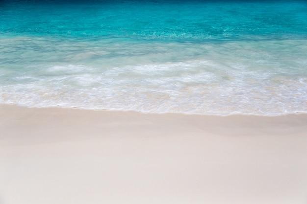 Plaża z białym piaskiem i turkusową wodą z falami