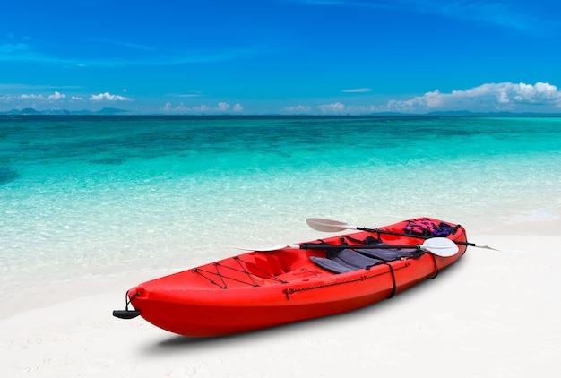 Plaża z błękitnym morzem i kajak z zewnętrznym oświetleniem słonecznym.
