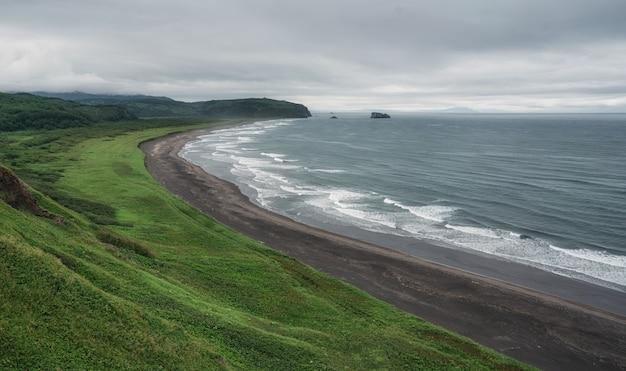 Plaża z czarnym piaskiem i falami w brzegu oceanu spokojnego na kamczatce