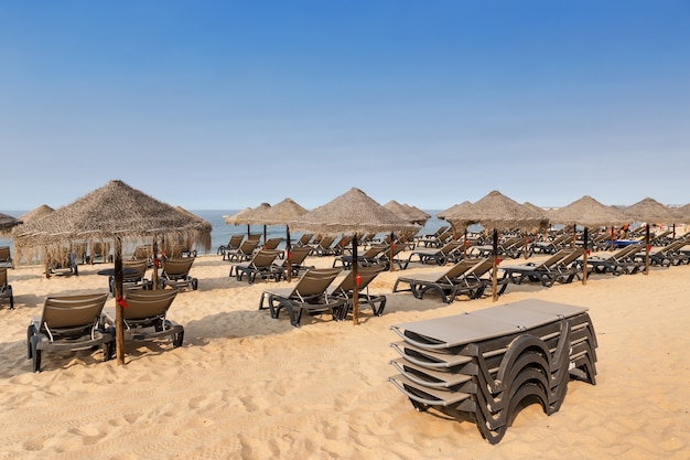 Plaża z leżakami i parasolami wakacyjnymi uczuciem, portugalia.