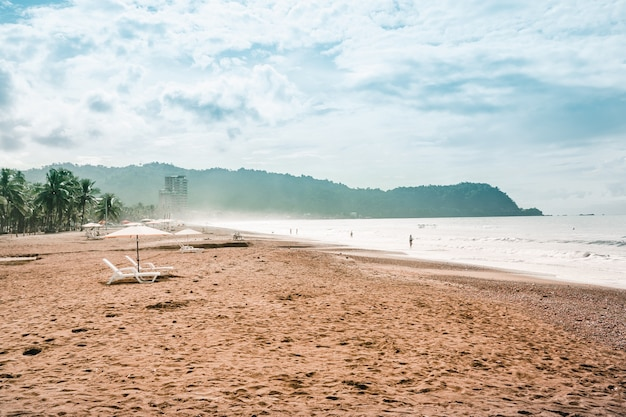 Plaża z leżakami i parasolami z dżunglą i górami. plaża jaco, kostaryka