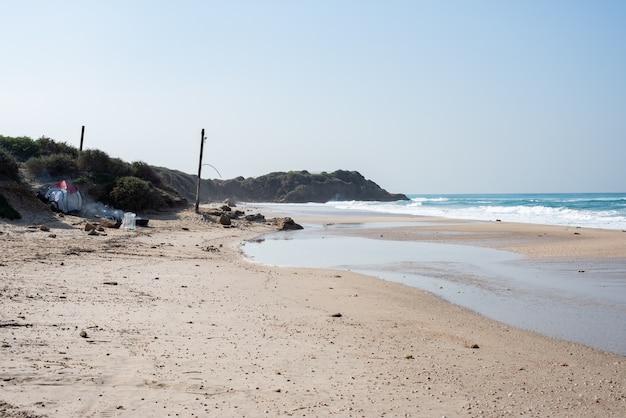 Plaża z ludźmi na niej otoczona morzem i wzgórzami pokrytymi zielenią w słońcu