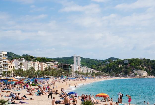 Plaża z morzem, piaskiem i ludźmi w hiszpanii.