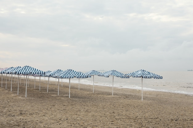 Plaża z parasolami. rano nad morzem. pusta plaża