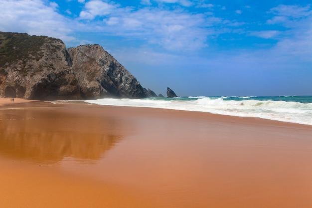 Plaża z piaskiem oceanu. skały w tle. fala surfingowa