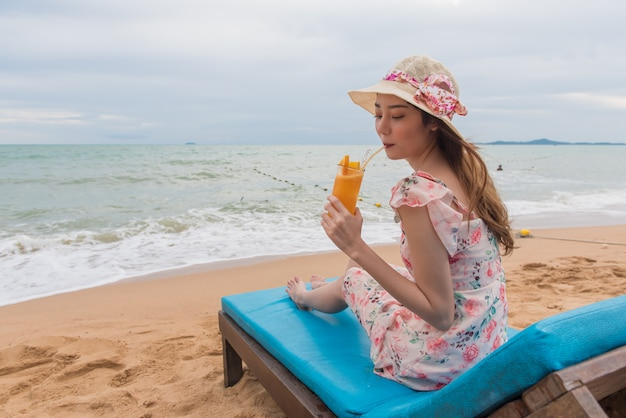 Plażowa urlopowa kobieta pije sok pomarańczowego ma zabawę na plaży.