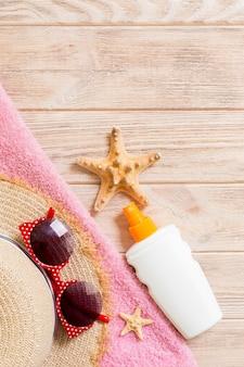 Plażowe akcesoria świeckich z miejscem na kopię. niebieski i biały ręcznik w paski, muszle, okulary przeciwsłoneczne, staw przeciwsłoneczny i butelkę kremu z filtrem na drewniane tła. koncepcja wakacji letnich.