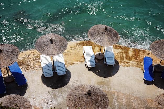 Plażowe parasole i krzesła na tle błękitnego morza na plaży w albanii. popularny ośrodek turystyczny nad morzem jońskim.