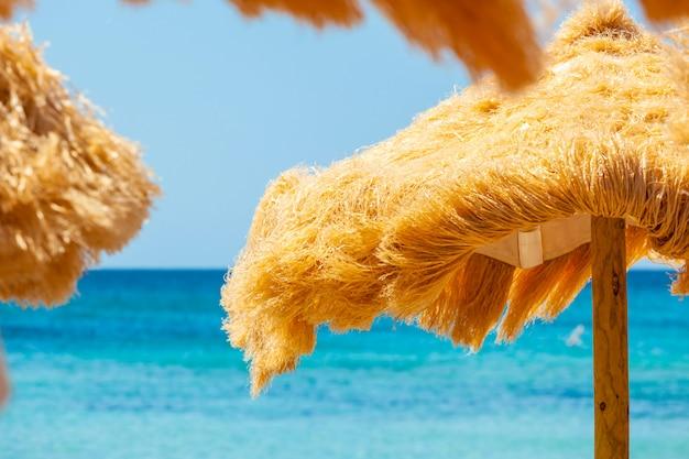 Plażowe piękne kryte strzechą parasole i turkusowe morze.