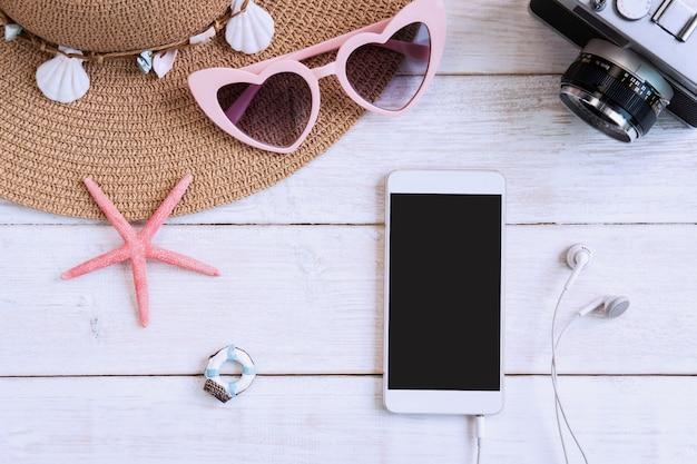 Plażowy kapelusz z podróży rzeczami i mądrze telefonem na białym drewnianym tle, wakacje letni pojęcie