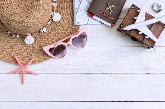 Plażowy kapelusz z podróży rzeczami na białym drewnianym tle