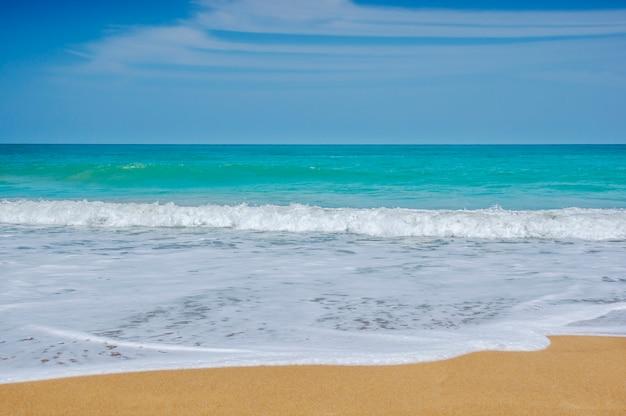 Plażowy piasek i błękitny morze w niebieskim niebie