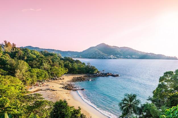 Plażowy piasek z błękitnym morzem i sunbeam w wieczór zaświecamy
