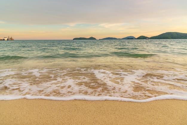 Plażowy zmierzch lub wschód słońca z kolorowym obłocznym niebem i światłem słonecznym