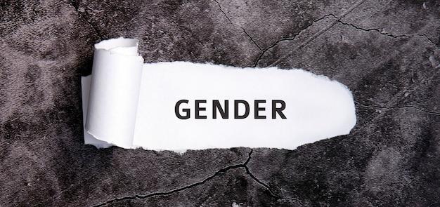 Płeć z podartym białym papierem na szarym betonowym stole.