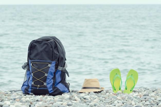 Plecak, czapka i klapki na kamienistej plaży. morze w tle