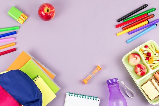 Plecak dziecięcy, pudełko śniadaniowe, butelka wody i przybory szkolne na drewnianym biurku
