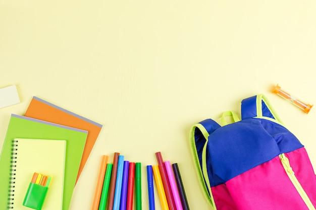 Plecak i przybory szkolne na drewnianym pulpicie, widok z góry