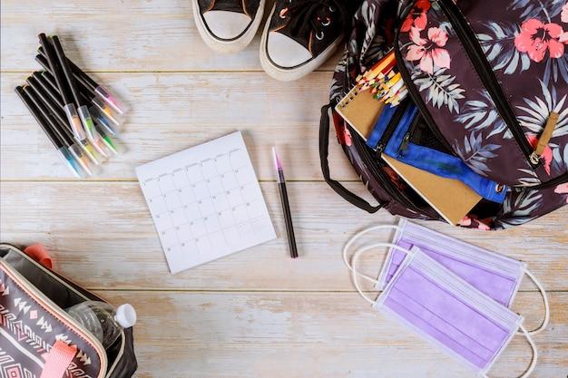 Plecak, kalendarz i maska na stole. koncepcja kwarantanny.