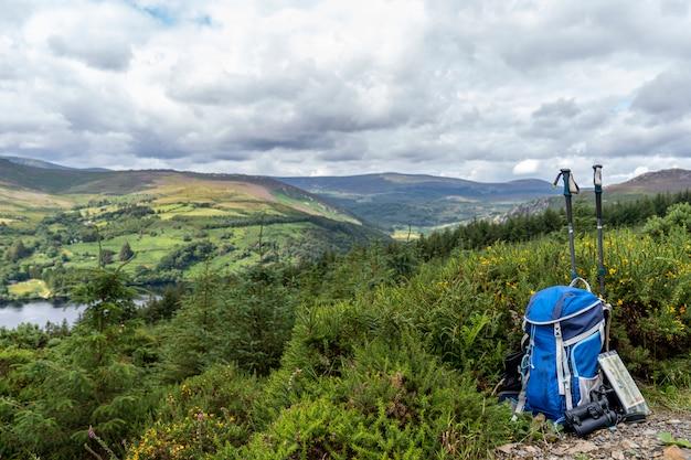 Plecak, lornetka, mapa i kije na górze, górski styl życia w irlandii.