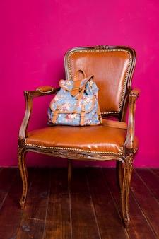 Plecak na fotelu w minimalistycznym wnętrzu z różową ścianą i drewnianą podłogą