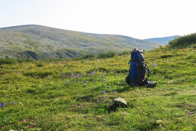 Plecak na łące trawy z górami. letni wędrówka motywacyjny obraz. miejsce na tekst
