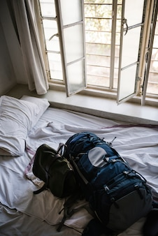 Plecak na łóżku w pokoju hotelowym rano