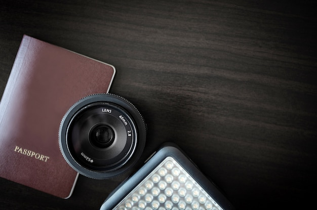 Plecak podróż i koncepcja fotografa na tle drewna z paszportem obiektywu i oświetleniem led w studio